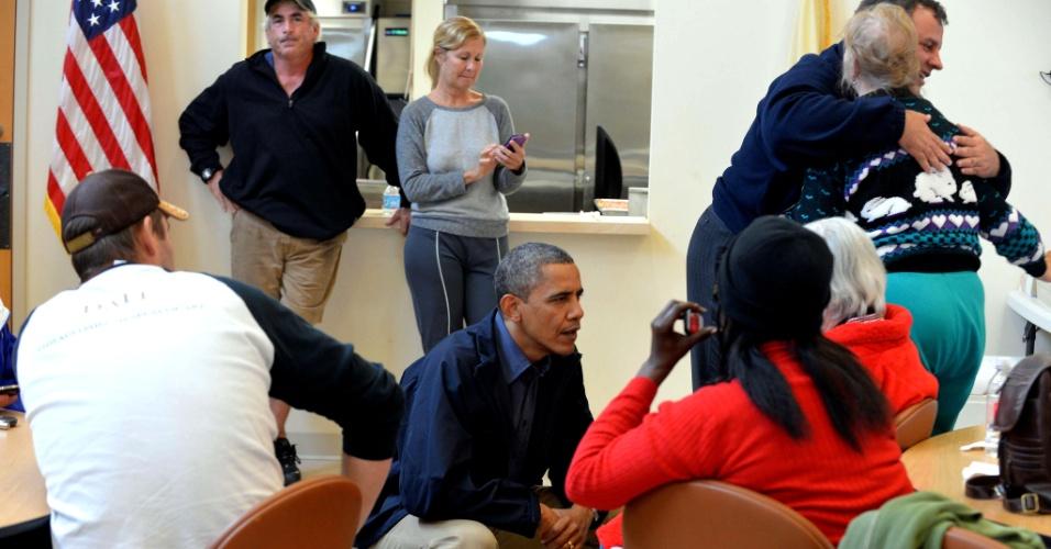 31.out.2012 - O Presidente Barack Obama e o governador de Nova Jersey, Chris Christie (em pé, à direita), conversam com vítimas do furacão Sandy em um abrigo em Brigantine. O Estado, costeiro, tem seu ponto mais continental a aproximadamente 80 km do Oceano Atlântico e foi o mais afetado pela tempestade