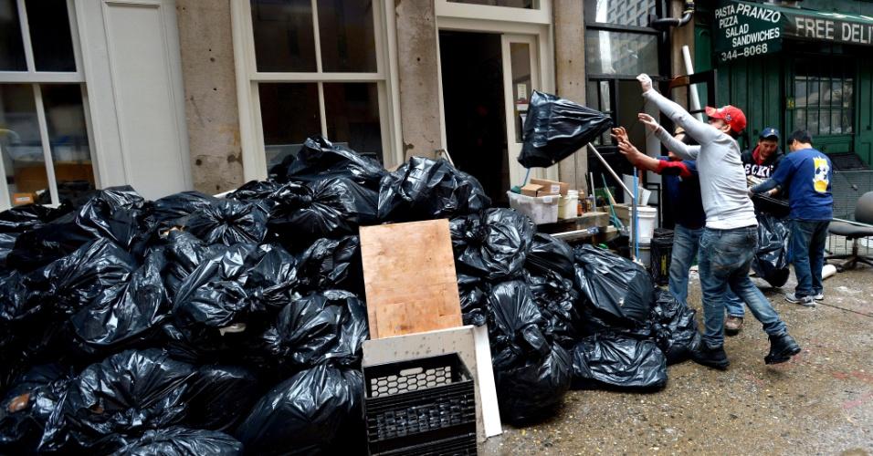 1°.nov.2012 - Homens jogam sacos cheios de lixo retirado de um porão inundado, no distrito financeiro de Nova York, enquanto a cidade vai, aos poucos, retomando a rotina. O governo dos EUA anunciou a aprovação de U$ 3,4 milhões em ajuda direta aos mais de 36 mil prejudicados pela passagem do furacão Sandy nos Estados de Nova York, Nova Jersey e Connecticut