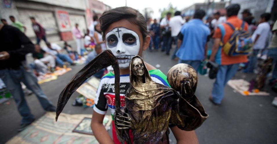 """1º.nov.2012 - Menina com o rosto pintado segura imagem de bronze da """"Santa Morte"""", a grande homenageada no """"Dia dos Mortos"""""""