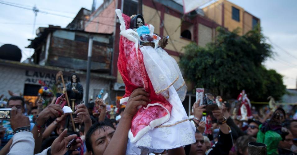 """1º.nov.2012 - Fiéis seguram imagens de bronze da """"Santa Morte"""", a grande homenageada no """"Dia dos Mortos"""""""