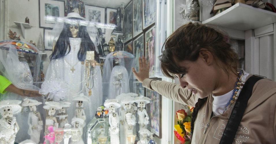 """1º.nov.2012 - Mulher reza diante de imagens da """"Santa Morte"""", a grande homenageada no """"Dia dos Mortos"""""""