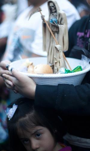 """1º.nov.2012 - Mulher segura bacia com oferendas e imagens da """"Santa Morte"""", a grande homenageada no """"Dia dos Mortos"""""""