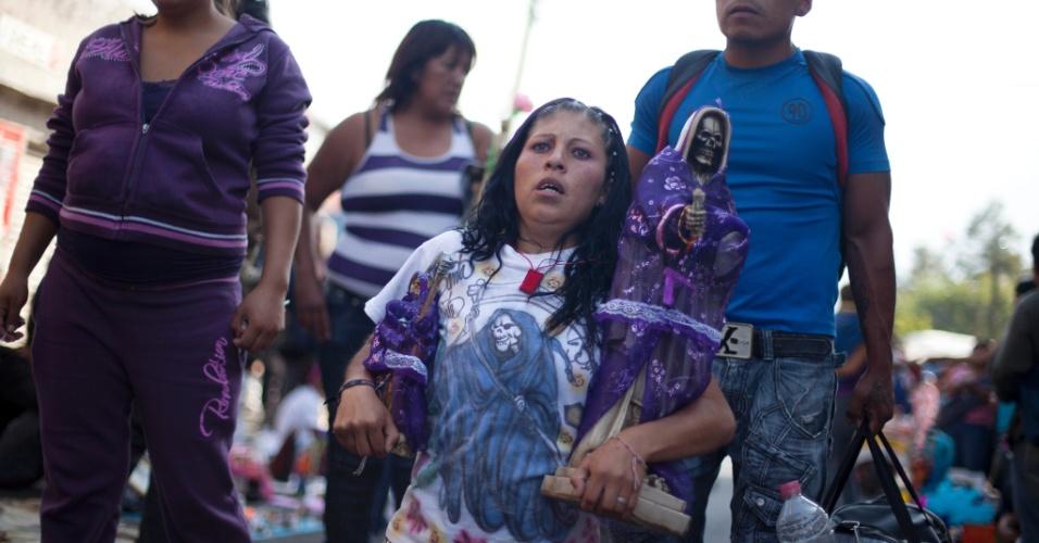"""1º.nov.2012 - Mulher ajoelhada segura imagem da """"Santa Morte"""", homenageada no """"Dia dos Mortos"""", em 31 de outubro, no México"""