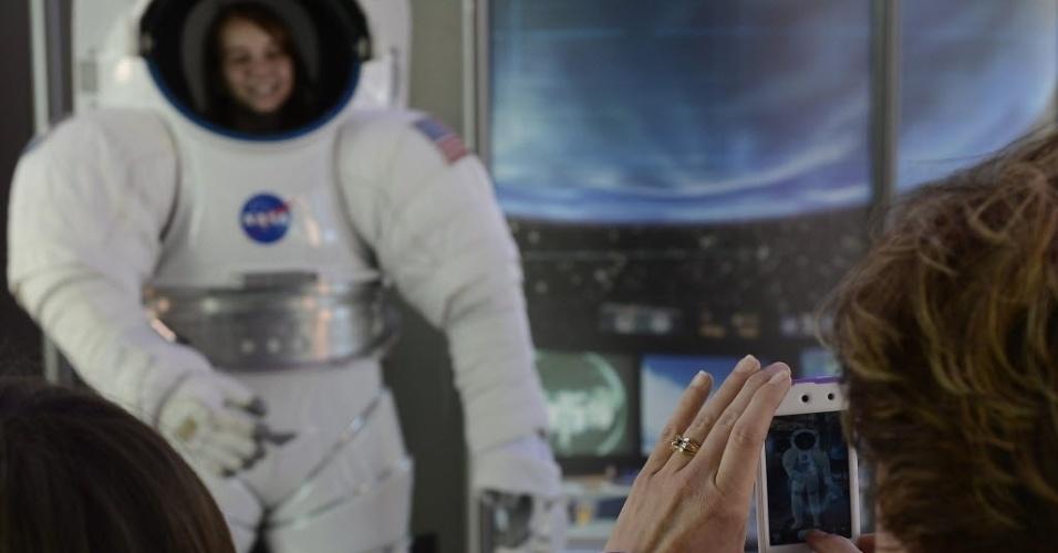 """1.nov.2012 - Mulher fotografa garota com roupa espacial durante abertura da exposição """"Endeavour: A História Califórnia"""" localizada no Centro de Ciências da Califória, em Los Angeles. A nave Endeavour tem 38 metros de comprimento e participou de 25 missões espaciais"""