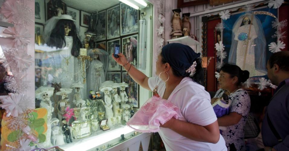 """1º.nov.2012 - Mulher tira foto de imagem da """"Santa Morte"""", homenageada no """"Dia dos Mortos"""", em 31 de outubro, no México"""