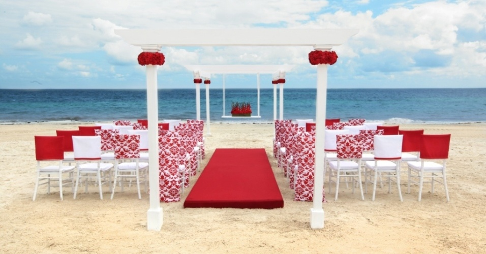 Estilo de decoração do pacote Coleção Romântica, da rede Palace Resorts (www.palaceresorts.com), em Cancún e Riviera Maia. A opção traz cadeiras brancas e vermelhas, caminho da noiva em vermelho e arco branco com flores. A cerimônia recebe, no máximo, 30 convidados