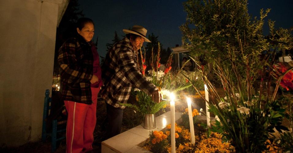 2.nov.2012 - Casal acende vela para parente morto no cemitério de San Gregório Atlapulco, na cidade do México