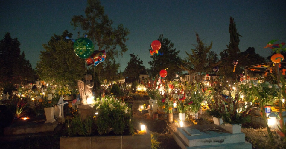 2.nov.2012 - Cemitério de San Gregório Atlapulco, na cidade do México, é enfeitado com flores e balões