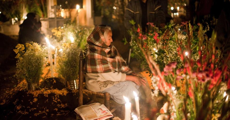 2.nov.2012 - Mulher idosa reza por parente morto no cemitério de San Gregório Atlapulco, na cidade do México