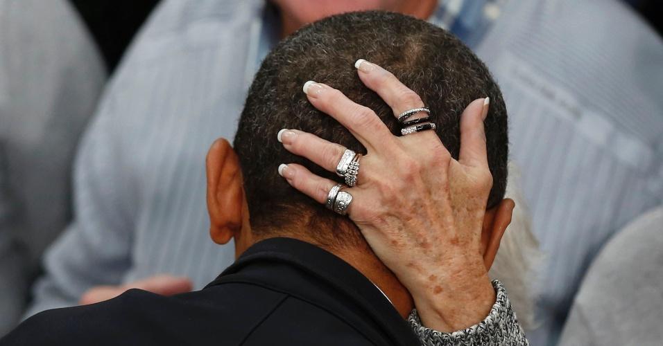 2.nov.2012 - Mulher segura cabeça de Barack Obama, democrata candidato à reeleição, enquanto o presidente cumprimenta apoiadores em evento de campanha em Ohio