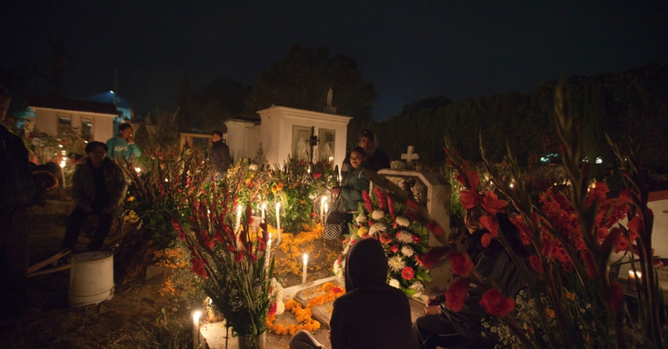 2.nov.2012 - Parentes de mortos passam a noite no cemitério de San Gregório Atlapulco, na cidade do México