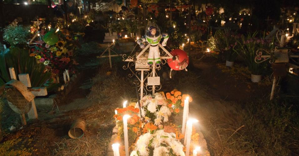 Túmulo de criança no cemitério de San Gregório Atlapulco, na cidade do México, é enfeitado com doces e brinquedos