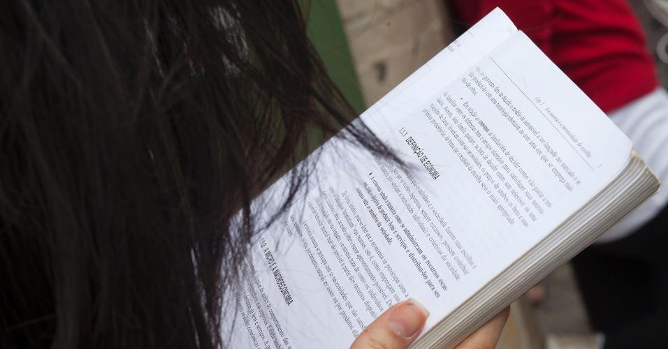 3.nov.2012 - Candidata lê enquanto espera a abertura dos portões dos locais de prova do Enem 2012, na zona oeste de São Paulo