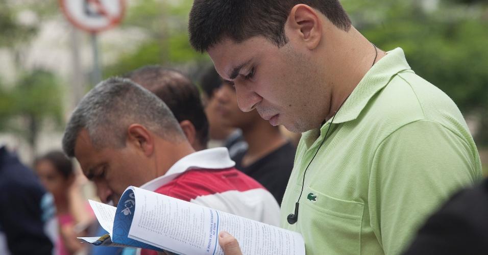 3.nov.2012 - Candidato lê enquanto espera a abertura dos portões dos locais de prova do Enem 2012, na zona oeste de São Paulo