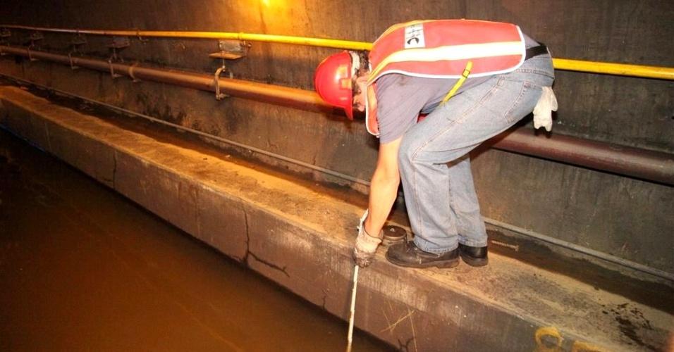3.nov.2012 - Funcionário da MTA (Autoridade Metropolitana de Trânsito) de Nova York mede a profundidade da água em túnel das linhas A e C do metrô, que passa sob o East River, entre Manhattan e Nova York