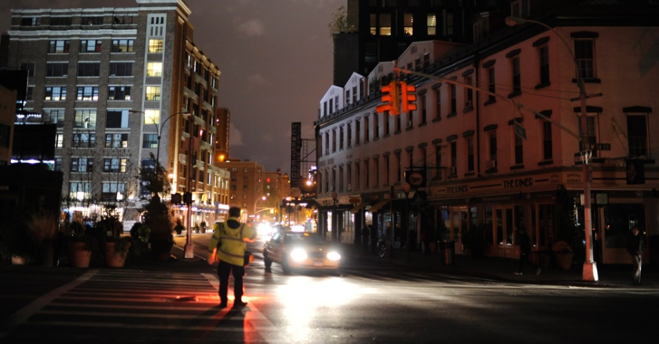 3.nov.2012 - Policial direciona tráfego de veículos em rua na região de Meat Packing, em Nova York (EUA). Quatro dias após passagem do furacão Sandy pela cidade, alguns pontos ainda estão sem eletricidade