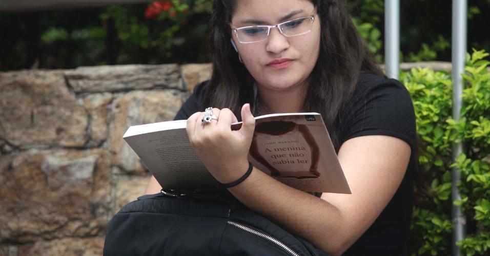4.nov.2012 - Candidata lê enquanto aguarda a abertura dos portões do segundo dia de provas do Enem 2012 em São Paulo