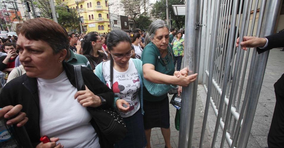 4.nov.2012 - Fiscal libera a entrada de candidatos para o segundo dia de provas do Enem 2012 na zona oeste de São Paulo