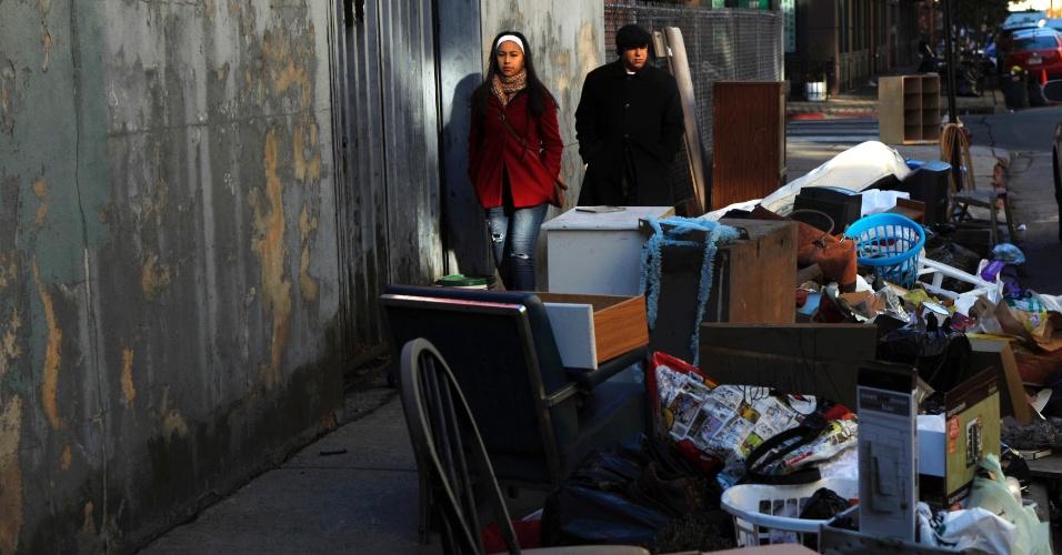 4.nov.2012 - Pessoas caminham em via de Nova Jersey, nos Estados Unidos, tomada por destroços da supertempestade Sandy. Vítimas na costa leste dos Estados Unidos lutam neste domingo (4) para se proteger do frio em meio à escassez de combustível e falta de energia na região