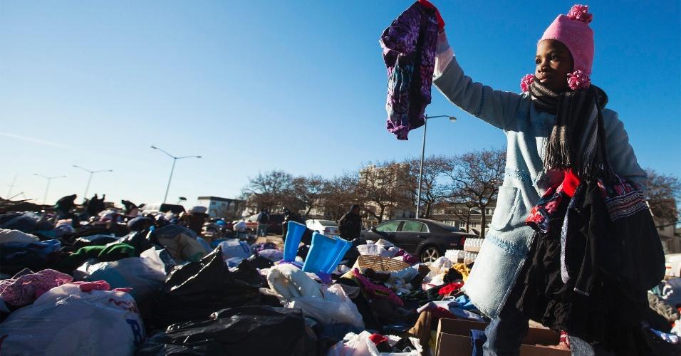 Menina ajuda família a separar roupas doadas para as vítima da tempestade Sandy no bairro do Queens, em Nova York. Vítimas da tempestade lutam contra o frio em meio a escassez de combustível e a falta de energia