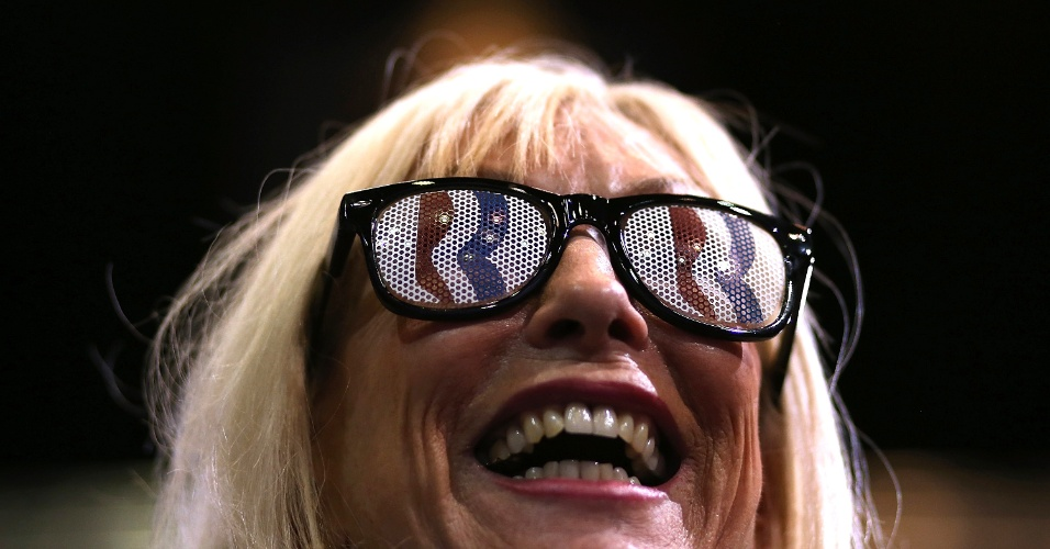 5.nov.2012 - Apoiadora do partido Republicano observa o ex-governador de Massachusetts e candidato republicano, Mitt Romney, discursar em campanha na universidade George Mason, em Fairfax, Virginia. Estado vizinho de Washington, Virginia possuí os condados com maior renda per capita dos EUA e é um dos Estados onde Romney e Obama seguem disputando eleitores, a um dia das eleições