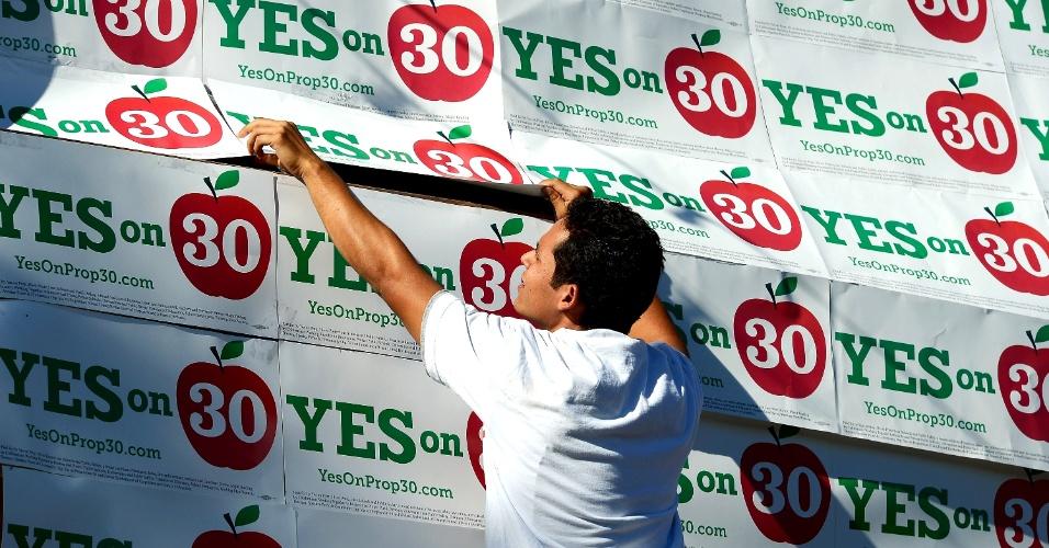 5.nov.2012 - Voluntário cobre parede de um minimercado com cartazes da proposta 30, antes de um comício em Panorama City, Califórnia. O plebiscito sobre a proposta que sugere o aumento de impostos sobre vendas e sobre rendas altas para incrementar o orçamento da educação pública no Estado será realizado junto à eleição presidencial