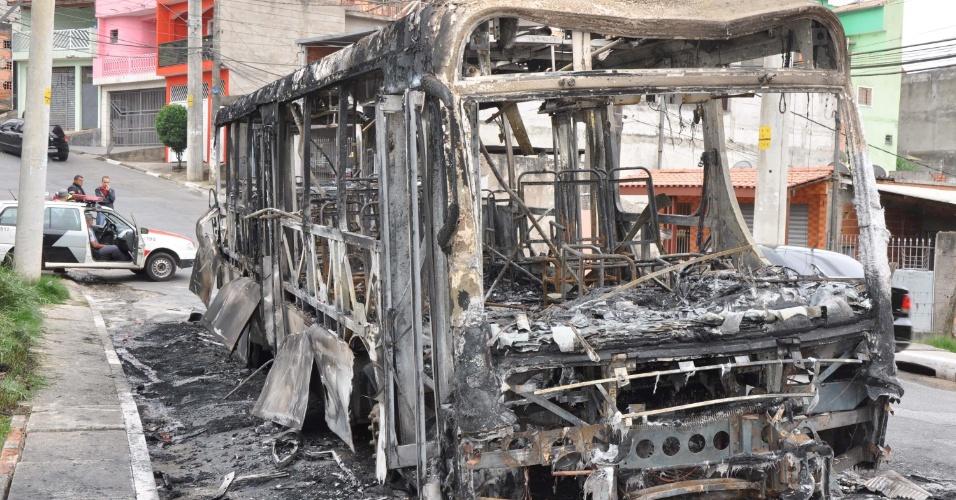 Policiais militares observam a carcaça de um ônibus que foi incendiado no bairro Iguatemi, zona leste de São Paulo, na noite deste domingo (4). De acordo com a polícia, um homem armado ordenou que os passageiros saíssem e ateou fogo no veículo