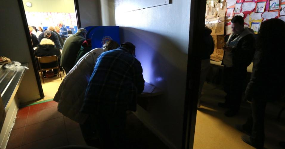 6.nov.2012 - Eleitores depositam seus votos em um local de votação parcialmente iluminado no bairro de Long Beach, Nova York. Locais afetados pela passagem do furacão Sandy tiveram que se adaptar para realizar as votações