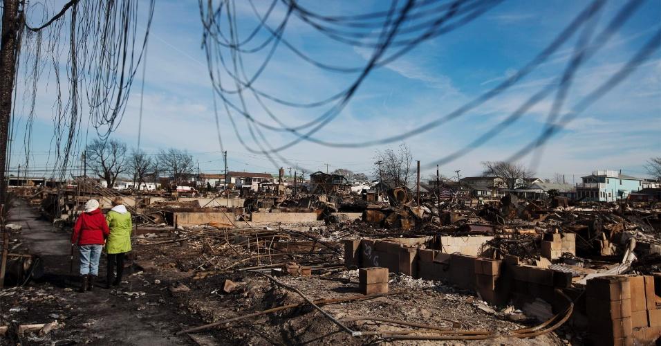 6.nov.2012 - Moradores caminham em meio aos escombros deixados pela passagem do furacão Sandy, em Queens, em Nova York, há uma semana