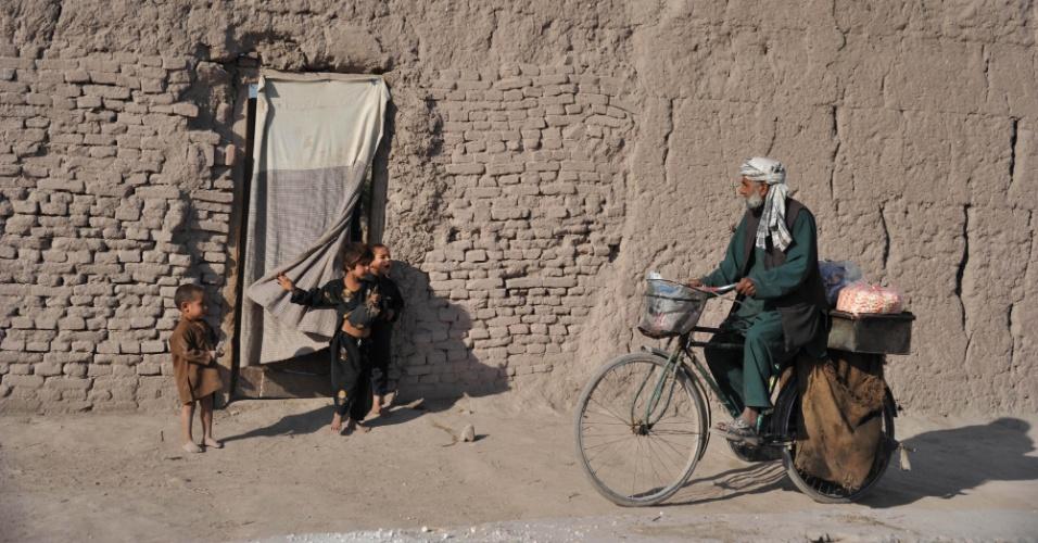 6.nov.2012 - Vendedor de pipoca afegão é observado por crianças enquanto anda de bicicleta nos arredores de Jalalabad
