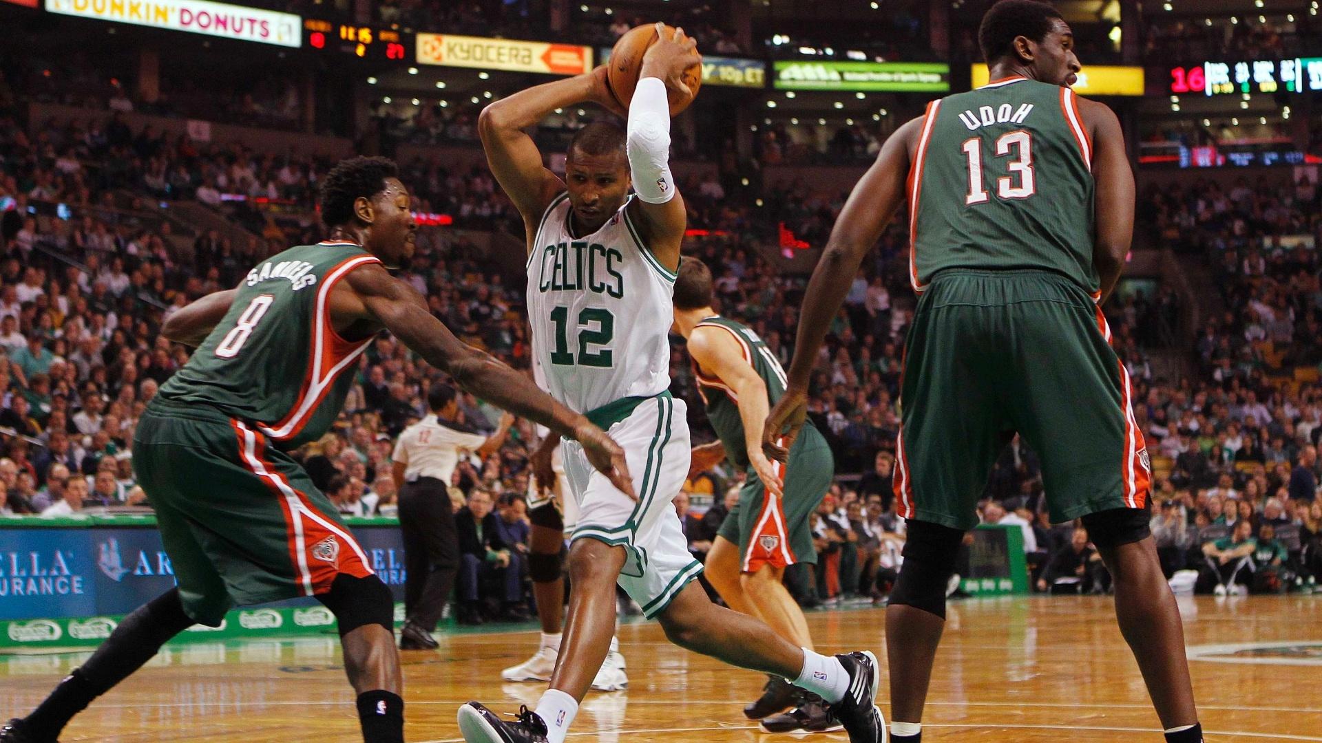 Leandrinho (c), do Boston Celtics, tenta passar pela marcação dos Bucks