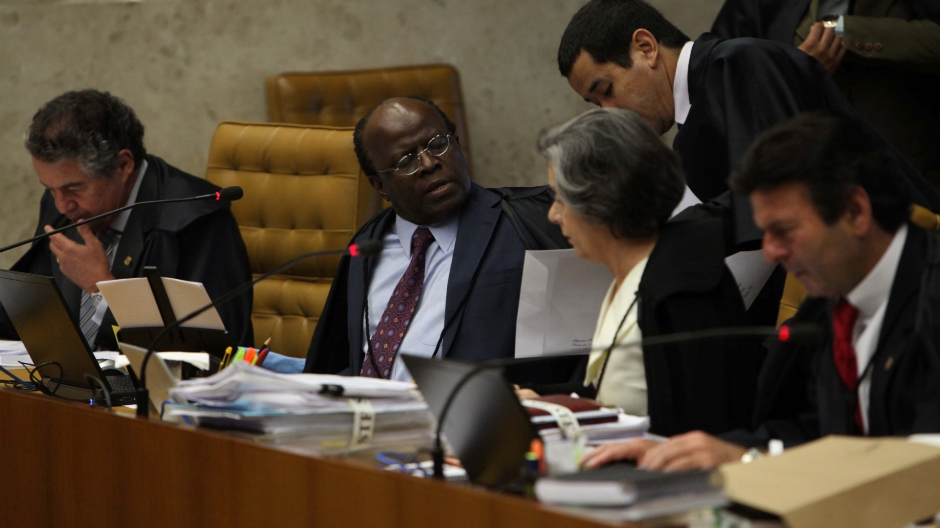 7.nov.2012 - O ministro-relator do processo do mensalo, Joaquim Barbosa(centro), aguarda incio da sesso de julgamento do mensalo ao lado de ministros do STF. Para agilizar a fixao das penas do rus condenados, Barbosa explica aos demais ministros que fez uma tabela para cada ru, especificando cada crime e os critrios usados para calcular cada pena