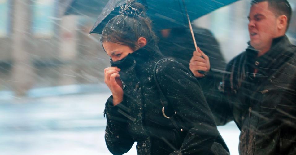 7.nov.2012 - Mulher protege o rosto durante tempestade de inverno que fez cair neve em Nova York (EUA) e ameaça trazer ventos perigosos e inundações à cidade, uma semana após a passagem do furacão Sandy
