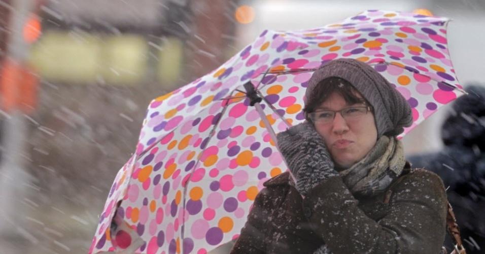 7.nov.2012 - Mulher sofre durante tempestade de inverno que fez cair neve em Nova York (EUA), e ameaça trazer ventos perigosos e inundações a cidade, uma semana após a passagem do furacão Sandy
