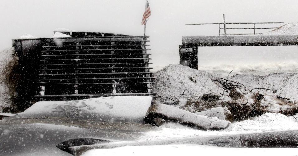 7.nov.2012 - Neve cobre trecho do calçadão da praia de Rockaway, no distrito do Queens, em Nova York, totalmente destruído pela força do furacão Sandy. O prefeito de Nova York, Michael Bloomberg, conta entre 30 e 40 mil pessoas desabrigadas que agora sofrem com o frio e ventos fortes trazidos por uma tempestade fria de nordeste
