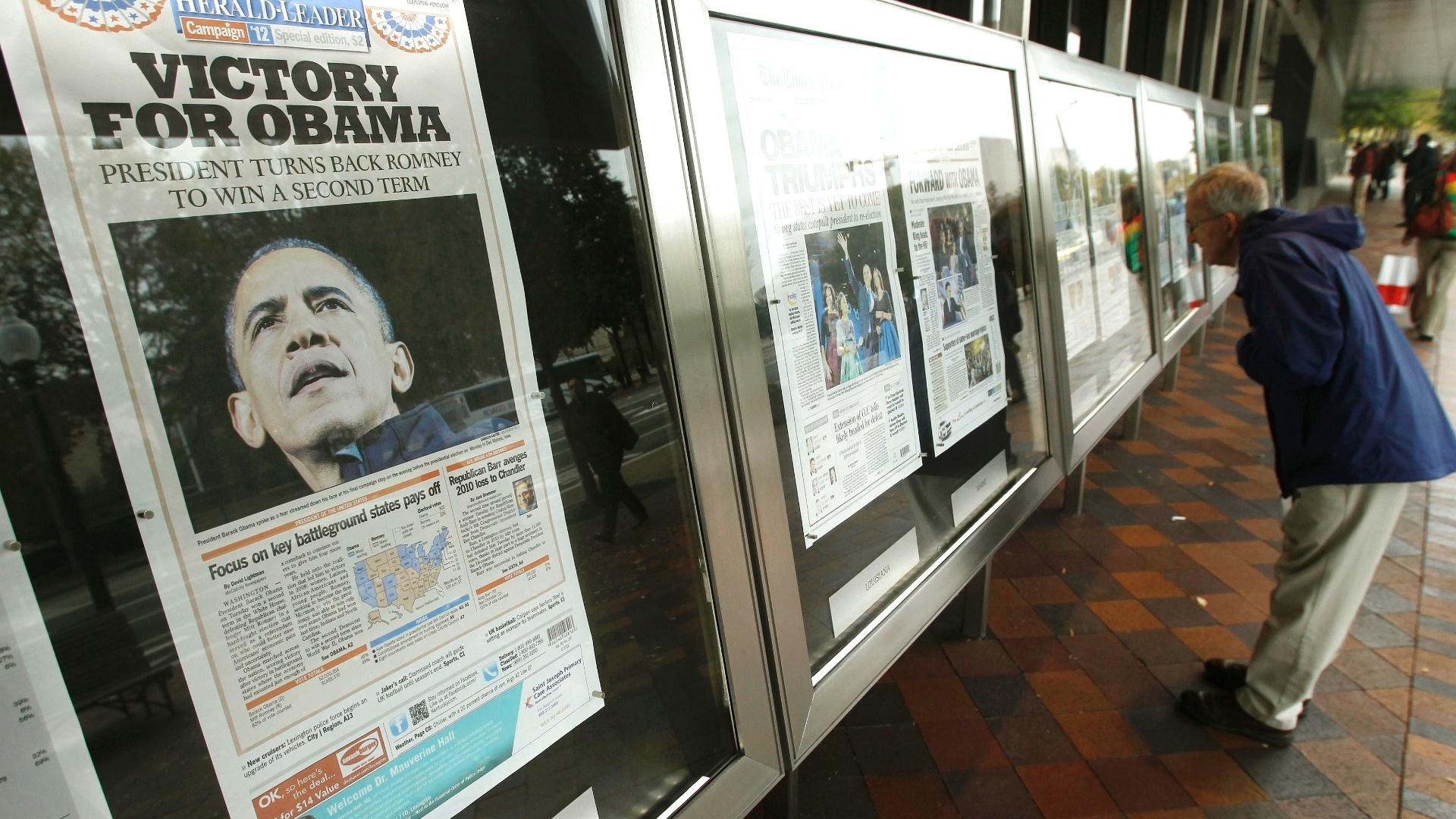 7.nov.2012 - Pessoas observam capas de jornais com manchetes da reeleição de Barack Obama no Newseum - museu da notícia - em Washington, DC. O presidente norte-americano tem pouco tempo para comemorar a vitória, pois enfrenta desafios econômicos e um congresso dividido, com maioria republicana