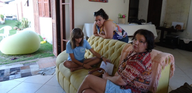 A estudante Isadora Faber com a mãe Mel (sentada no sofá) e a tia Joice (de pé) hoje pela manhã