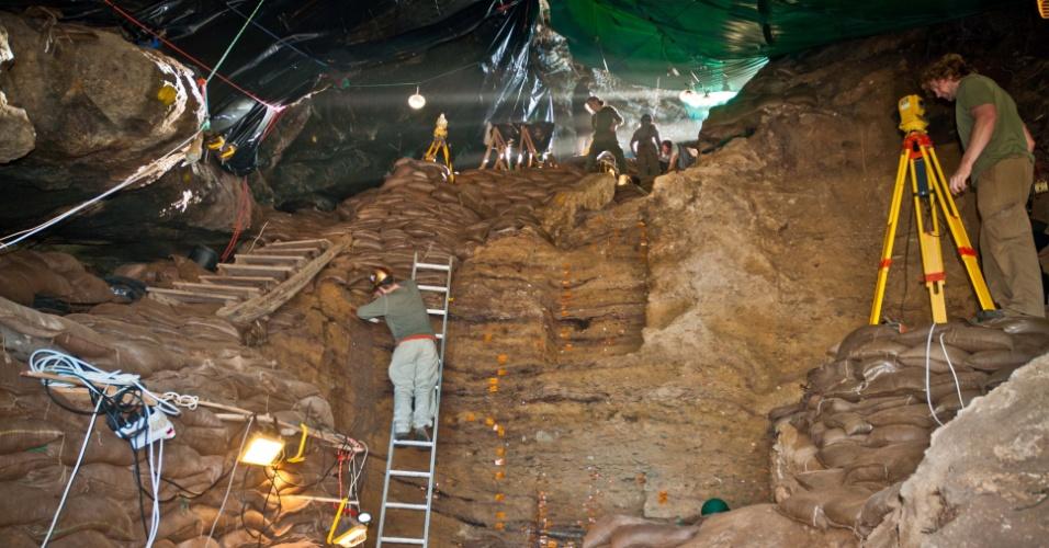 """8.nov.2012 - Equipe escava caverna perto da Baía de Mossel, no litoral da África do Sul, onde foram achadas lâminas microlíticas e produzidas com lascas de pedra aquecidas. Os artefatos demonstram que os homens das cavernas usavam """"tecnologia"""" há cerca de 71 mil anos atrás, e não há 60 mil como se pensava. Publicada na revista Nature, a pesquisa foi liderada por Curtis Marean, da Universidade do Estado do Arizona, nos Estados Unidos, e contou com a ajuda de pesquisadores da África do Sul, da Austrália e da"""