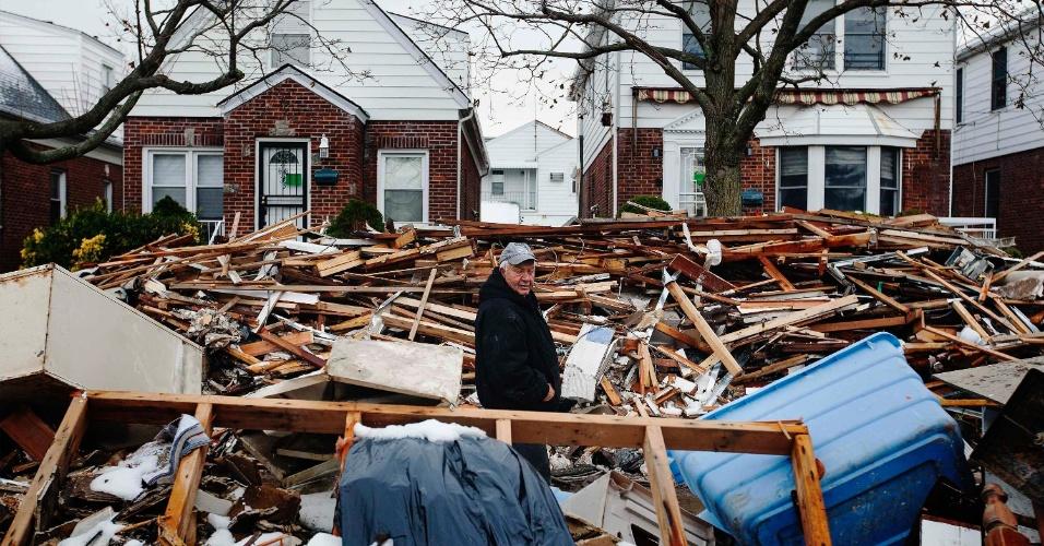 8.nov.2012 - Homem caminha em meio ao entulho ainda não removido das casas danificadas por enchentes durante o furacão Sandy no bairro Queens of Belle Harbor, em Nova York