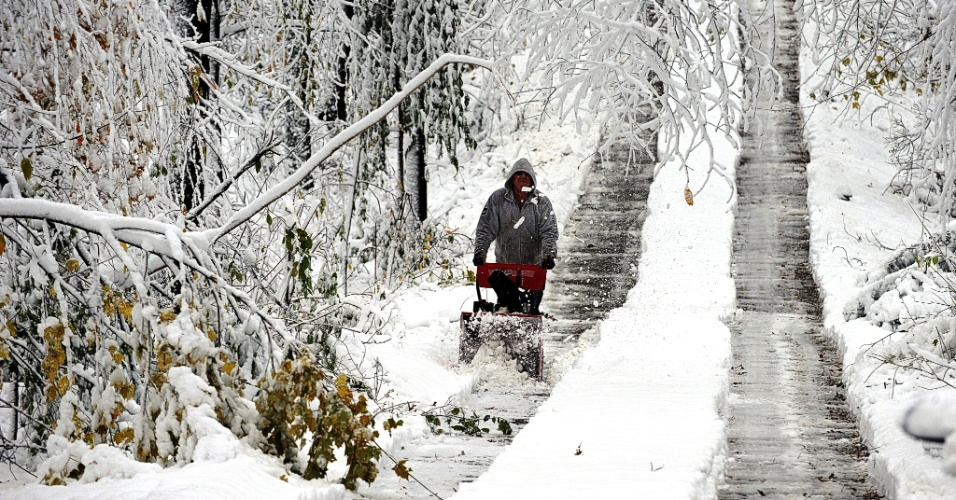 8.nov.2012 - Morador da cidade de Dix Hills, no Estado de Nova York, limpa passagem de veículos margeada de árvores derrubadas pela nevasca e fortes ventos, trazidos por uma tempestade fria de nordeste à região nesta madrugada