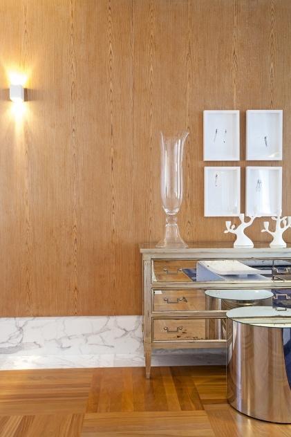 À frente do painel de madeira, com iluminação de arandela, o aparador de efeito espelhado da Artzzi se destaca.  O apartamento no bairro Cambuí, em Campinas (SP), tem projeto de interiores e decoração assinado pela arquiteta Elaine Carvalho
