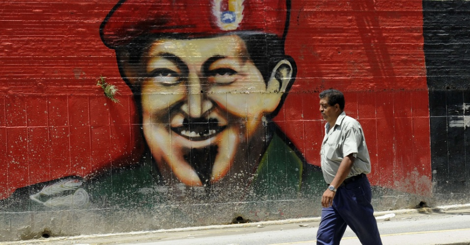 6.out.2012 - Homem caminha ao lado de muro com a imagem do presidente venezuelano, Hugo Chávez, em Caracas Chávez foi reeleito para um quarto mandato neste ano, com 54,6% dos votos. O presidente está há 14 anos no poder