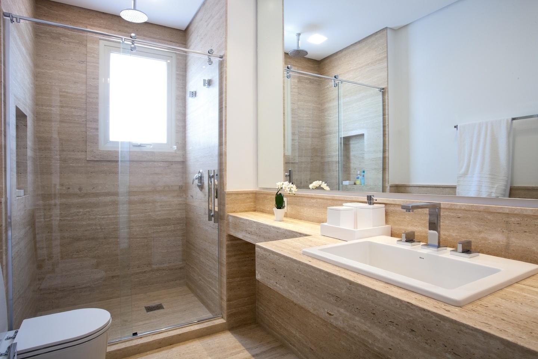 No banheiro, o revestimento do piso, paredes do box e bancada são de mármore travertino romano, da Marmoraria Balcroft, com acabamento