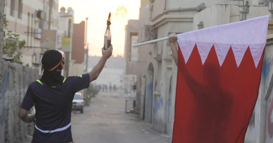 10.nov.2012 - Bareinitas carregam coquetel molotov e a bandeira do Bahrein em meio a confronto com a polícia em Samaheej, no Bahrein. Milhares de pessoas participavam de marcha no funeral de Ali Abbas Radhi, de 16 anos, quando manifestantes entraram em confronto com forças de segurança