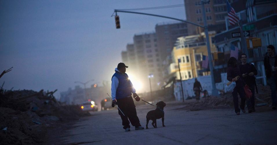 10.nov.2012 - Homem caminha com cachorro na região do Queens, em Nova York (Estados Unidos). O prefeito Michael Bloomberg anunciou que neste sábado haveria uma espécie de mutirão para ajudar a limpar os estragos causados pela tempestade