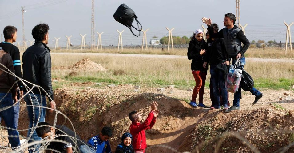 Homem joga mala para outro enquanto passam por vala após cruzarem a fronteira da Síria com a Turquia