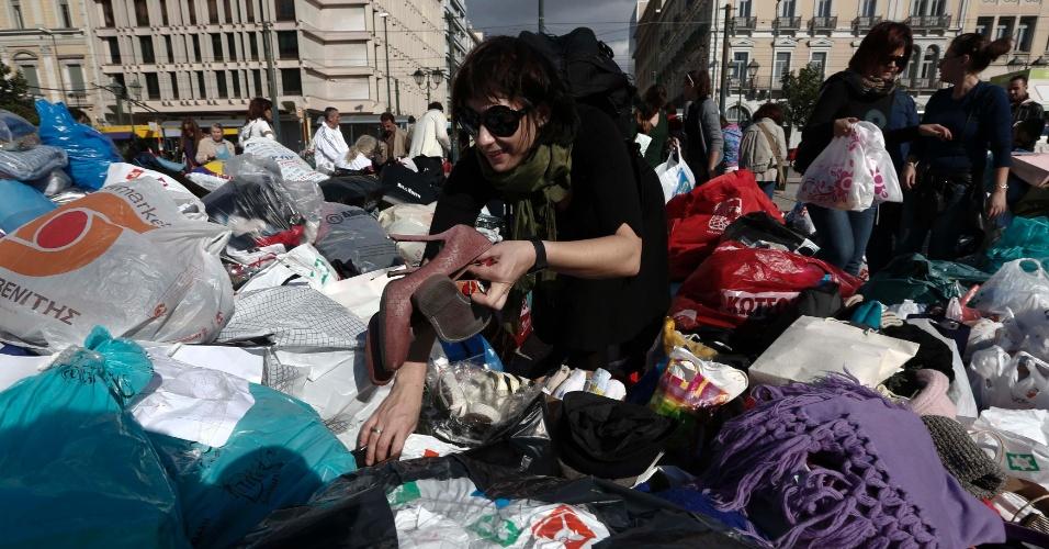 Mulher recolhe sapatos de uma pilha de roupas em uma ação de doação realizada na praça central de Atenas