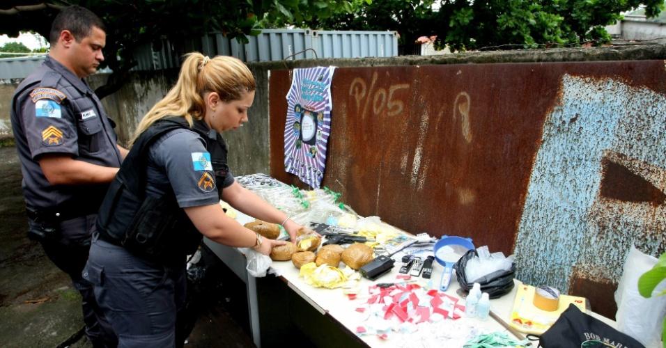 Policiais organizam material apreendido em operação nas favelas de Antares e Rola, em Santa Cruz, zona oeste do Rio
