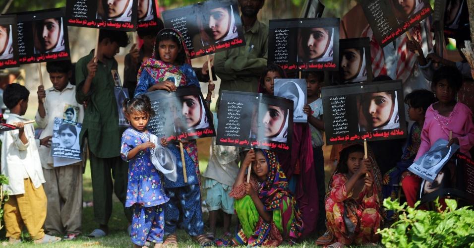 """Vítimas de enchentes no Paquistão participam do """"Dia da Malala"""", segurando fotos da jovem ativista paquistanesa Malala Yousafzai, baleada por talebãs"""
