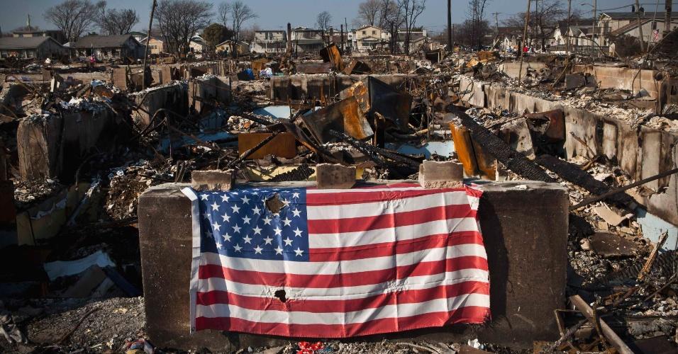 11.nov.2012 - Bandeira dos Estados Unidos é colocada em local do bairro do Queen atingido pelo furacão Sandy, em Nova York, nos Estados Unidos, neste domingo (11)